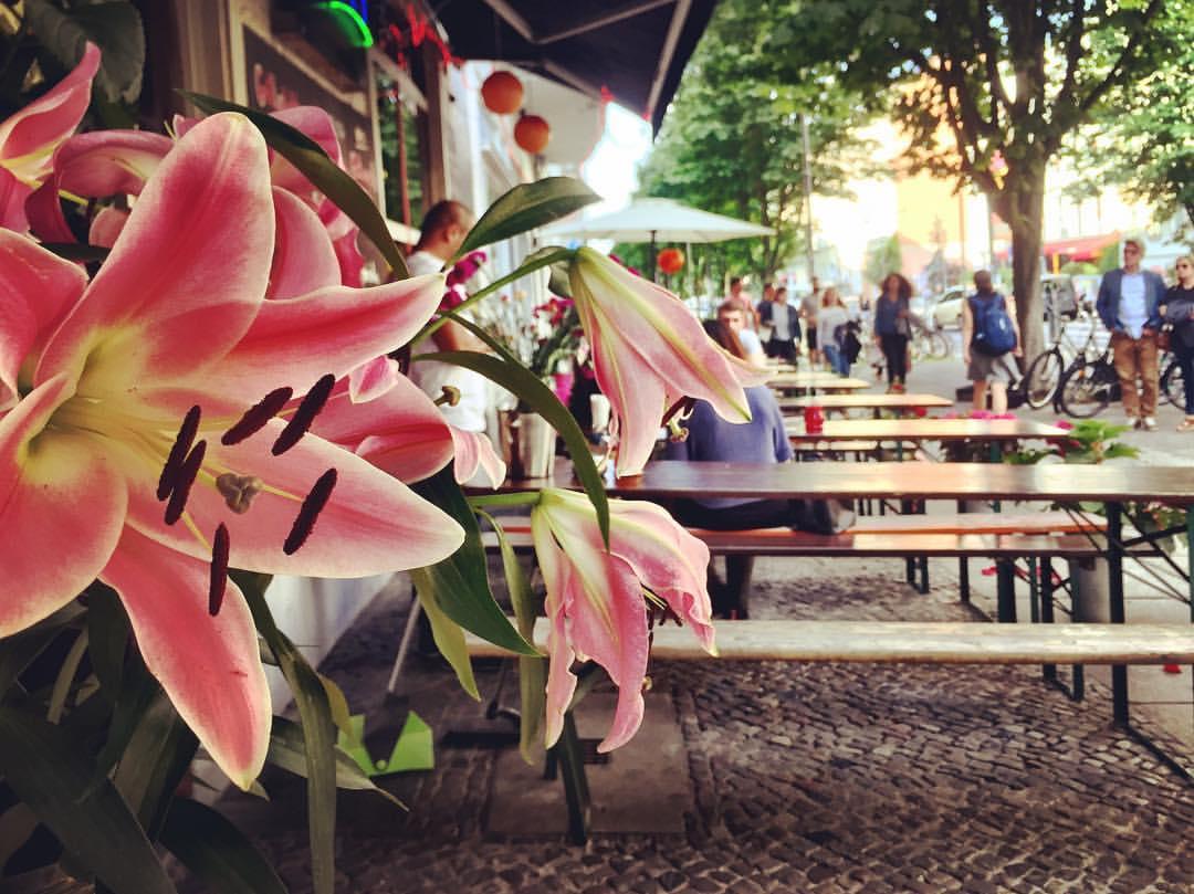 #paracegover Descrição para deficientes visuais: a imagem mostra um restaurante que está sempre decorado com muitas e belíssimas flores. Em primeiro plano, um vaso de lírios cheirosíssimos. Há bicicletas estacionadas na calçada e pessoas caminhando ao lado das mesas compridas de madeira. — at Modern Graphics Kastanienallee.