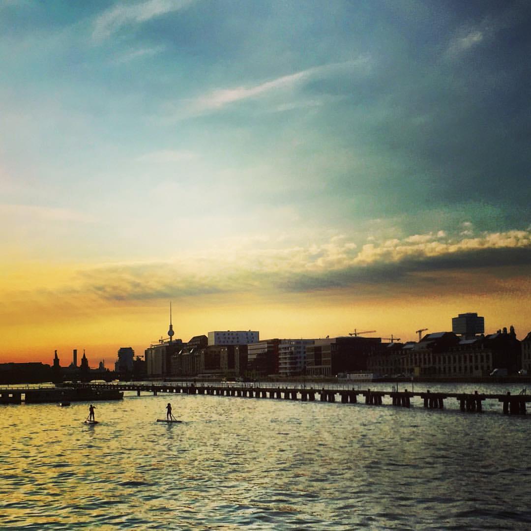 #paracegover Descrição para deficientes visuais: a imagem mostra um por-do-sol espetacular visto de uma margem do rio Spree. Ao fundo, na skyline da cidade, é possível ver a torre de tv. Duas pessoas fazem stand up paddle. — at Molecule Man (sculpture).