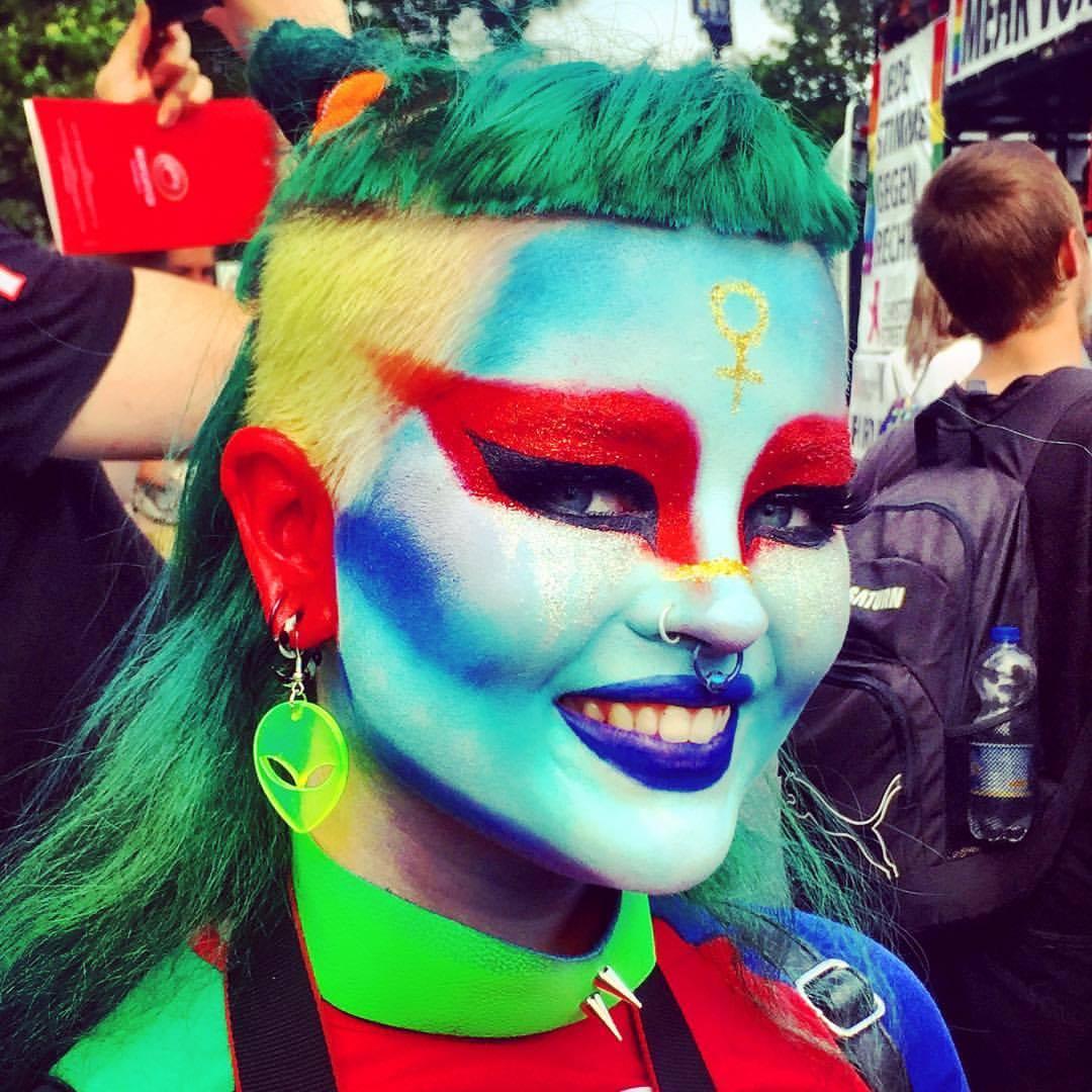 #paracegover Descrição para deficientes visuais: a foto mostra uma moça com os cabelos semi-raspados e coloridos nas cores verde e amarelo; a maquiagem, caprichadíssima, é uma máscara azul-clara com sombras azuis, lábios azuis e olhassem vermelho e marinho. Ela tem belos olhos azuis, traz o símbolo do feminino na testa em dourado e está sorrindo. Os brincos, de plástico verde neon, mostra o rosto de um ET. Há piercings no nariz, a roupa também é colorida.