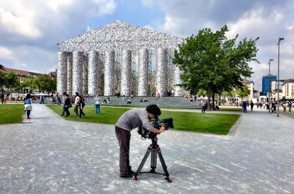 Um homem opera uma filmadora sobre um tripé. Ao fundo, o Partenon de livros.