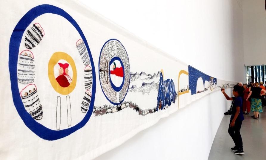 A imagem mostra o bordado preso à parede para a exposição.