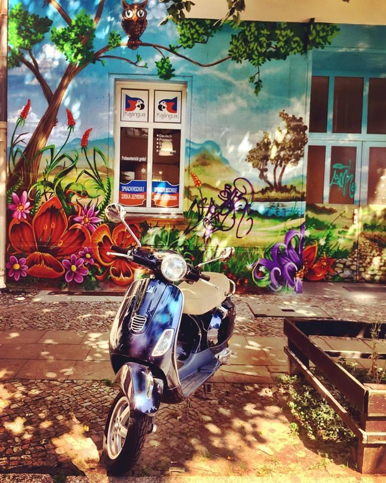 #paracegover Descrição para deficientes visuais: a imagem mostra uma vespa azul estacionada na sombra de uma calçada coberta de árvores. O prédio atrás é grafitado com desenhos bem coloridos retratando um jardim florido. As folhas da árvore desenhada se confundem com as de verdade. A foto ficou parecendo um desenho. — at All Style Tattoo Berlin.