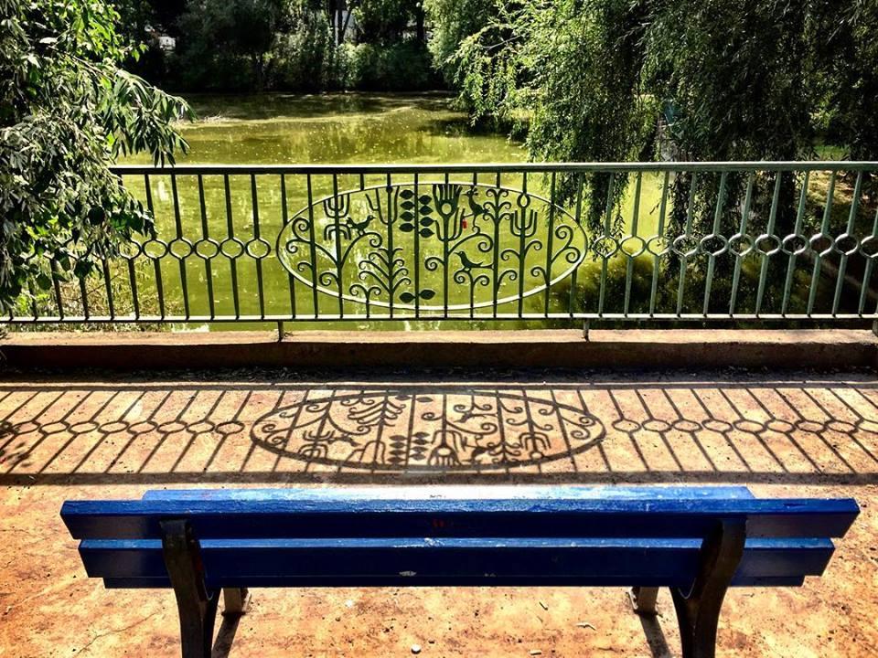 #paracegover Descrição para deficientes visuais: a imagem mostra um banco de praça azul marinho visto de costas. Ele está num parque, de frente para um lago. Na frente dele há uma grade de proteção com um desenho delicadíssimo de pássaros em galhos. A sombra da grade é projetada no chão, parecendo um bordado de luz. Adoro essas pequenas delicadezas que fazem o mundo mais bonito... — at Fennpfuhl.