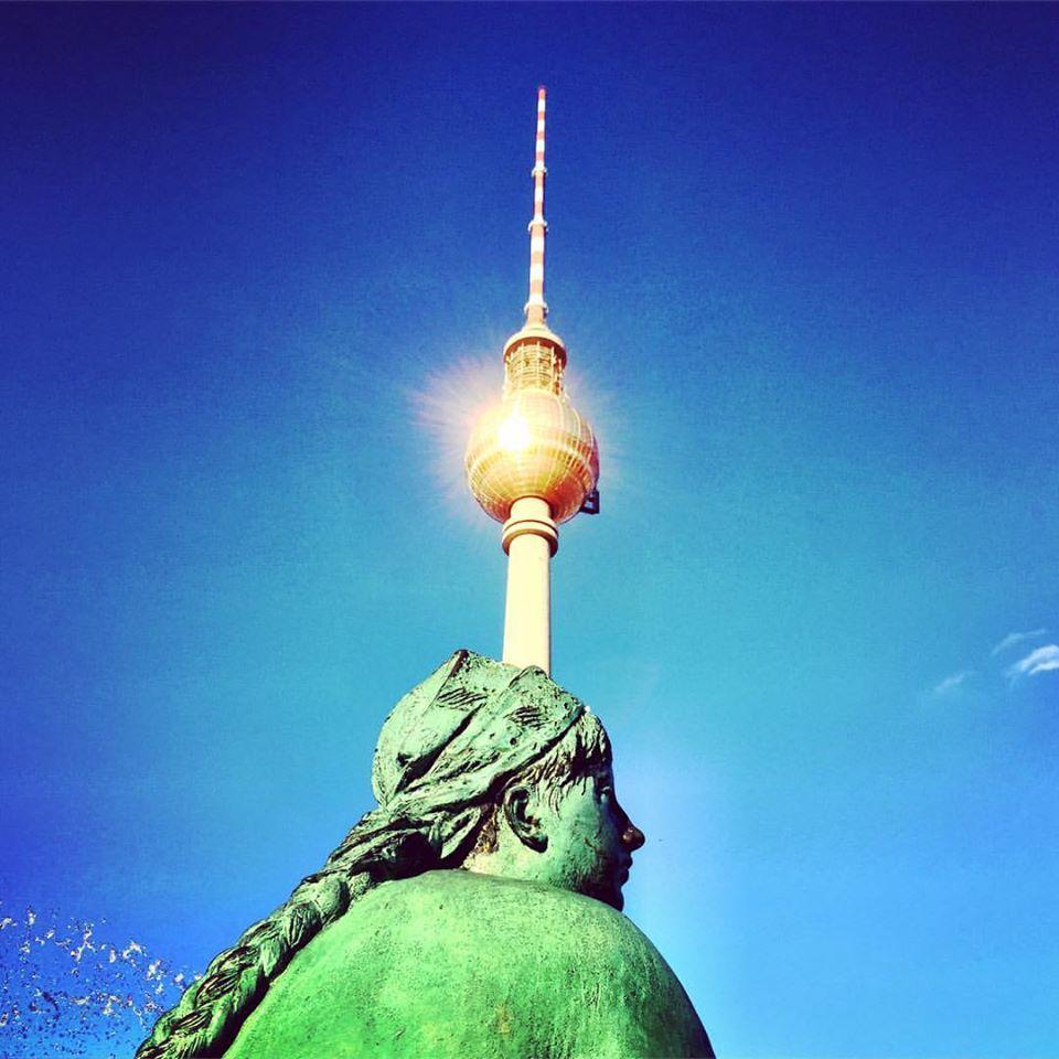 #paracegover Descrição para deficientes visuais: a imagem mostra uma das esculturas da fonte de netuno que representa uma mulher. Ela é verde e está de costas. Ao fundo, a torre de TV cuja esfera espelhada recebe em cheio a luz do sol, parece o próprio. — at Neptunbrunnen.