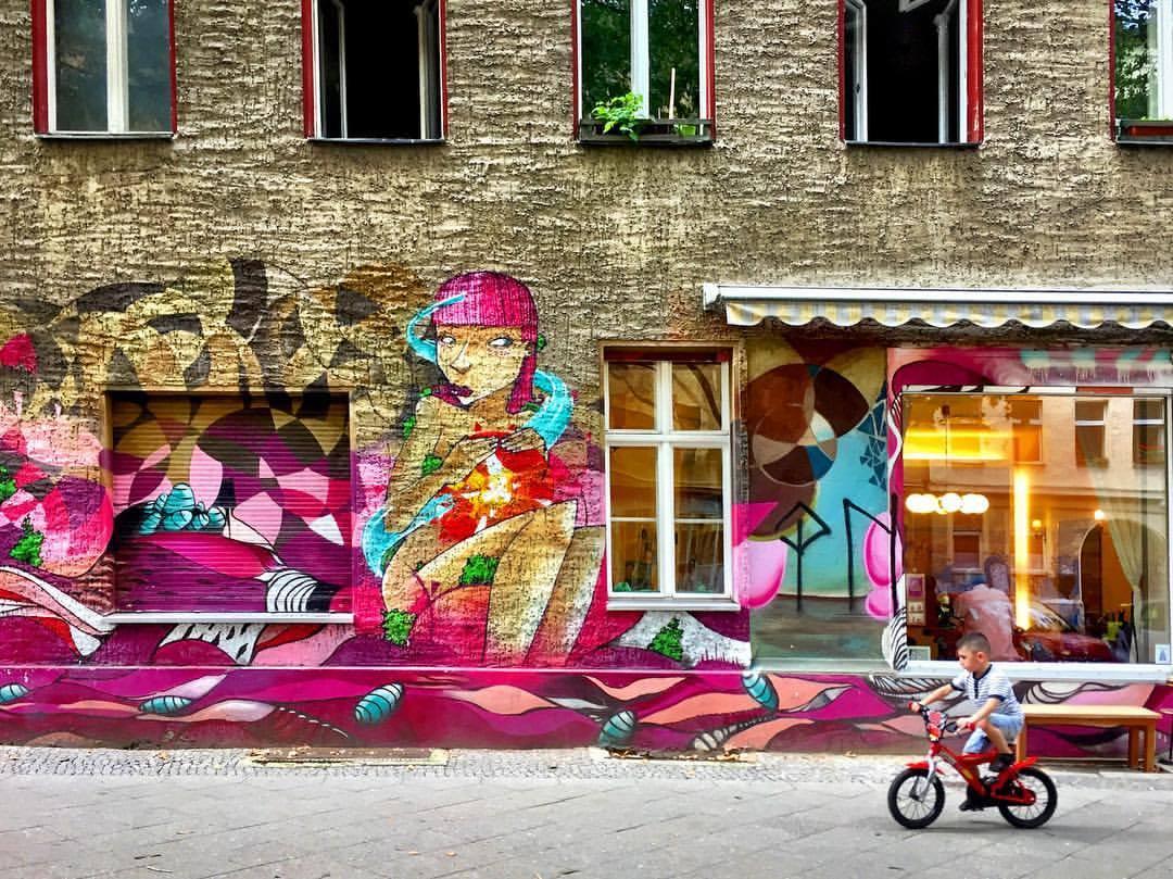 #paracegover Descrição para deficientes visuais: a imagem mostra a fachada de um prédio grafitada só até a altura das janelas do prédio. O fundo é bege escuro e o grafite é em tons de rosa, magenta e vinho. Uma criança passeia de bicicleta pela calçada larga. No canto direito aparece uma vitrine de um salão de cabeleireiro. — at Eastern Bull 1453.