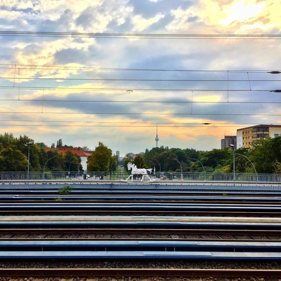 #paracegover Descrição para deficientes visuais: a imagem mostra os trilhos de uma estação de trem urbano. Posicionada paralelamente às linhas, uma escultura representando um cavalinho de balanço construído com tábuas de madeira pintadas de branco destaca-se na paisagem. Ao fundo pode-se ver a Torre de TV sob o céu alaranjado. — at Berlin Greifswalder Straße station.