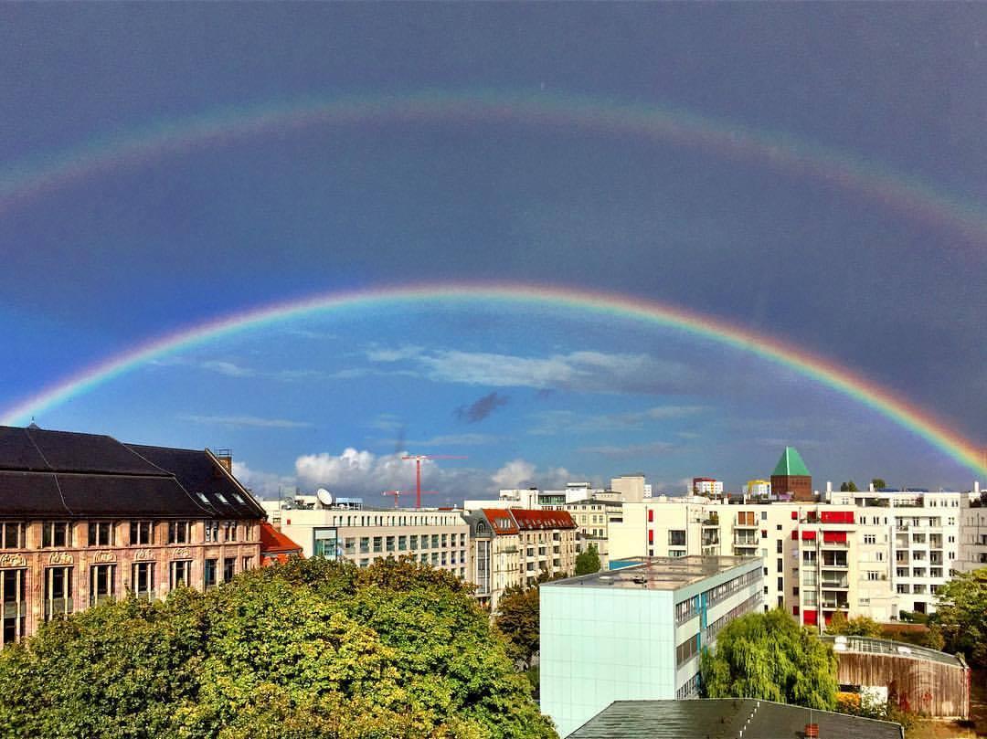 #paracegover Descrição para deficientes visuais: a imagem mostra um arco-íris duplo. Na parte de baixo, o céu está azul; na parte de cima, bem nublado. Também aparecem prédios e árvores. — at Berlin Mitte.