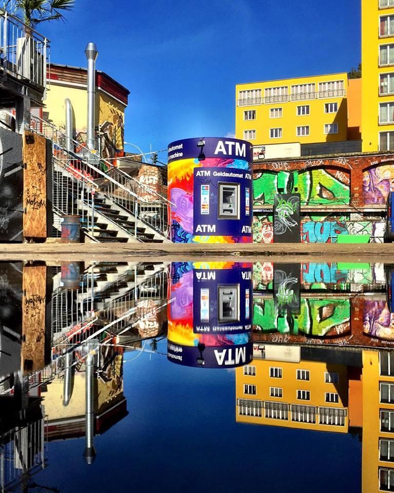 #paracegover Descrição para deficientes visuais: a imagem mostra um pátio todo grafitado com uma instalação cilíndrica colorida no centro, onde funciona um terminal bancário. O azul do céu parece pintado. Toda a cena se reflete na poça d'água em frente. — at RAW-Gelände.
