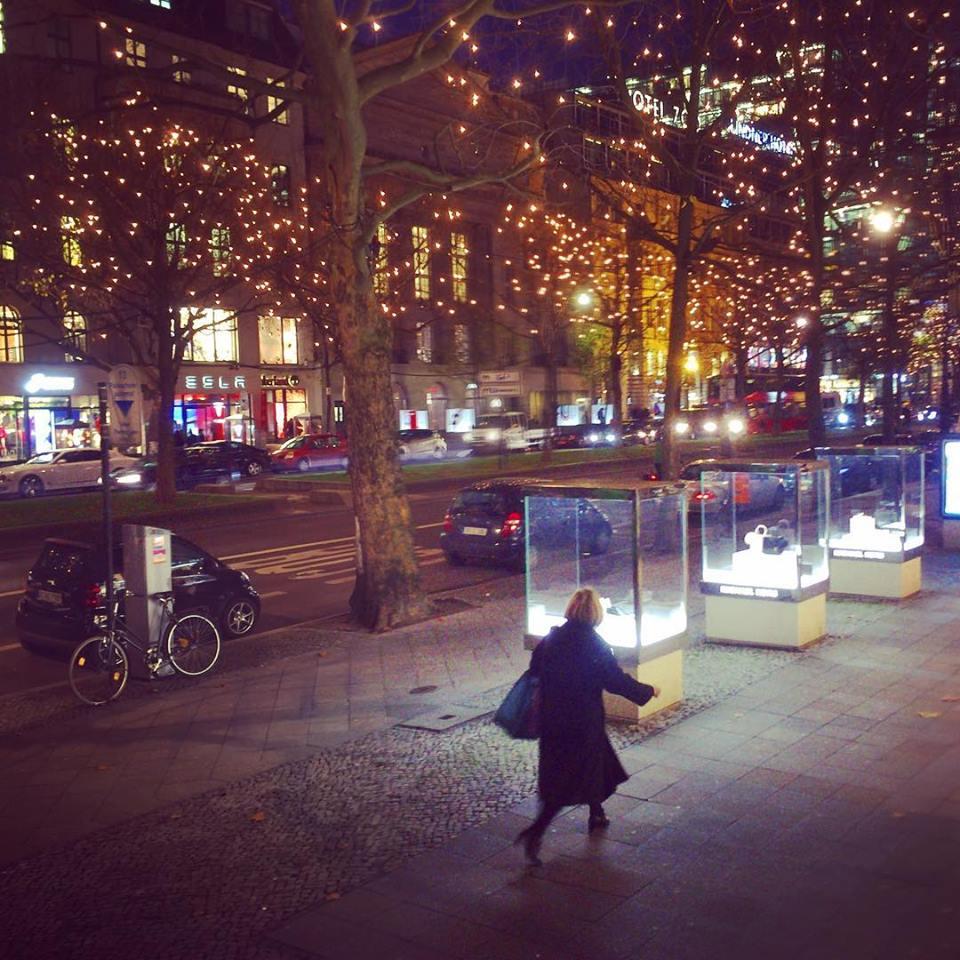 #paracegover Descrição para deficientes visuais: a imagem mostra uma mulher caminhando em uma calçada larga com vitrines de vidro em forma cúbica. Está escuro e as árvores são iluminadas por milhares de pequenas luzes.