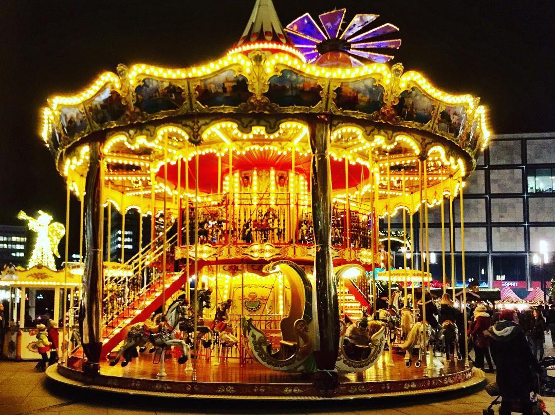 #paracegover Descrição para deficientes visuais: a imagem mostra um carrossel iluminado (é noite). O fundo é vermelho e as luzes são amarelas. A foto foi tirada na Alexanderplatz.