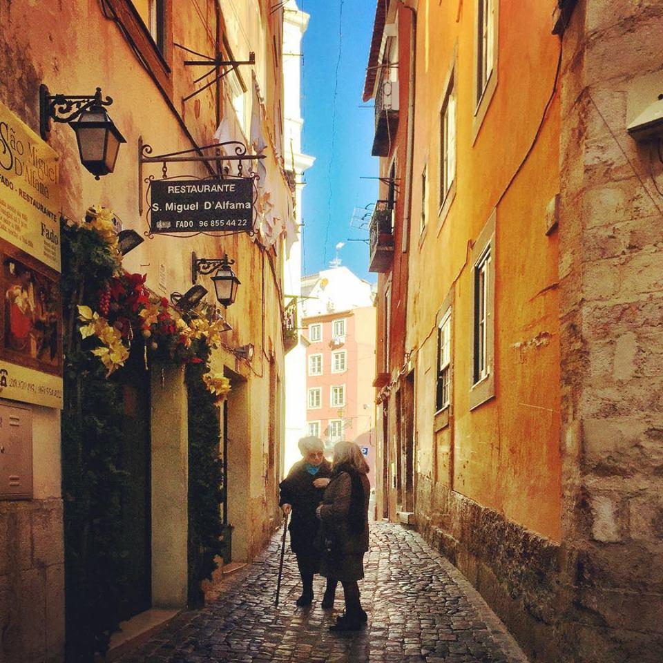 #paracegover Descrição para deficientes visuais: a imagem mostra duas senhoras portuguesas conversando em um beco do bairro Alfama. O dia está cinematográfico! — in Alfama, Lisboa, Portugal.