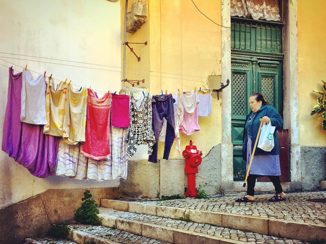 #paracegover Descrição para deficientes visuais: a imagem mostra uma senhora descendo a rua com sua bengala. Na calçada, um varal cheio de roupas coloridas. — at Barco Do Garcês- Retiro Do Peso Pesado.