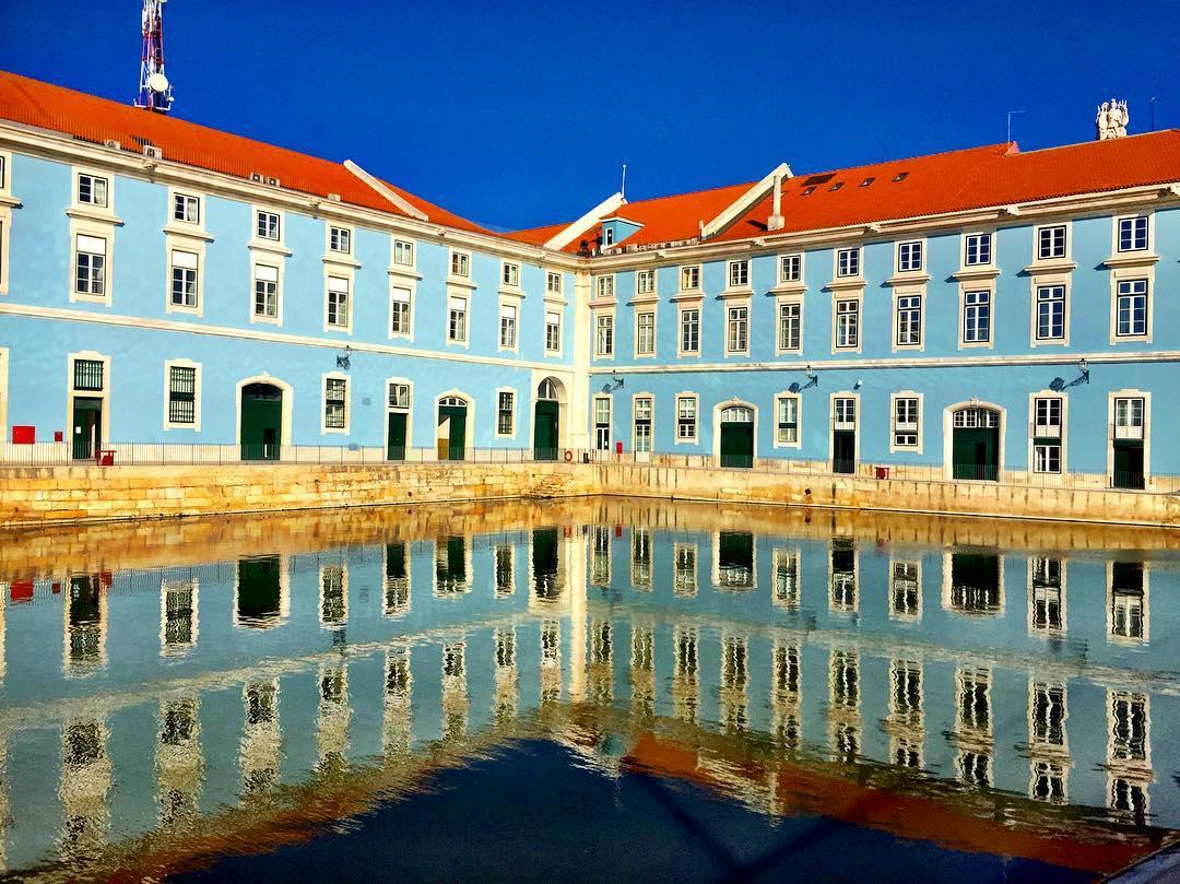 #paracegover Descrição para deficientes visuais: a imagem mostra o prédio da marinha portuguesa, todo azul, refletido no espelho d'água. — at Ribeira das Naus.