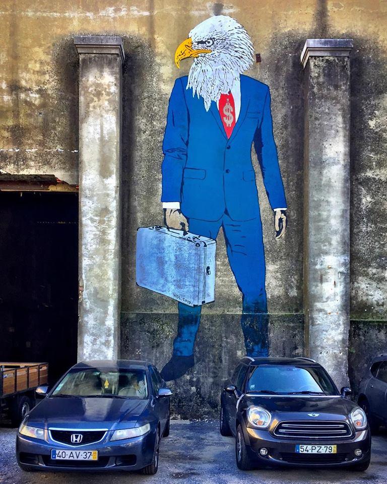#paracegover Descrição para deficientes visuais: a imagem mostra a porta de um galpão que funciona como garagem. Nas paredes altas da fachada há um grafite representando uma águia de terno azul marinho cuja gravata traz um cifrão estampado. Elas está pintada entre duas colunas e há dois carros estacionados em frente. Parece que os carros são seus sapatos. — at LXFactory.