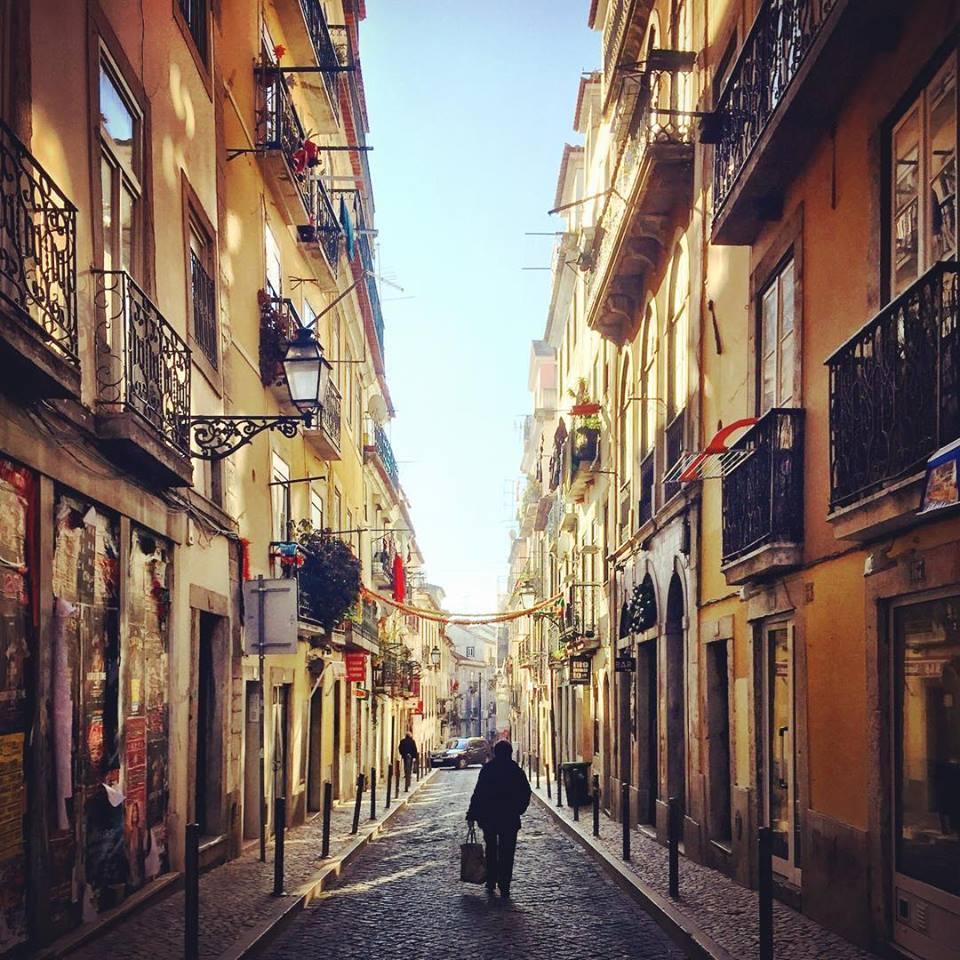 #paracegover Descrição para deficientes visuais: a imagem mostra uma senhorinha de costas caminhando por uma rua típica do Bairro Alto-Chiado. A luz está perfeita. — at Rua da Rosa.