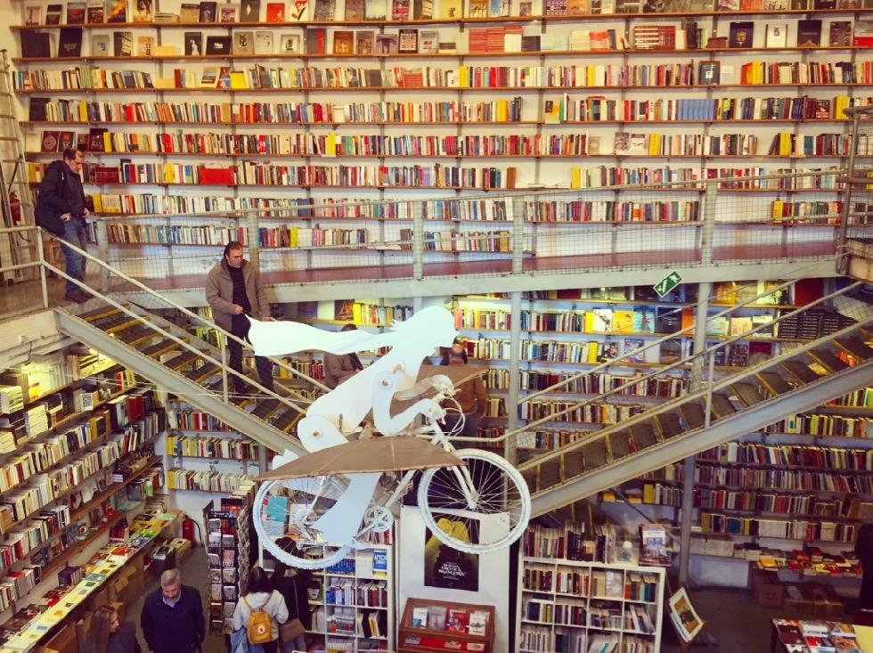 #paracegover Descrição para deficientes visuais: a imagem mostra o interior de uma livraria com suas estantes lotadas em dois pavimentos. Pendurada no teto, uma escultura de uma bicicleta voadora ❤️ — at Livraria Ler Devagar.