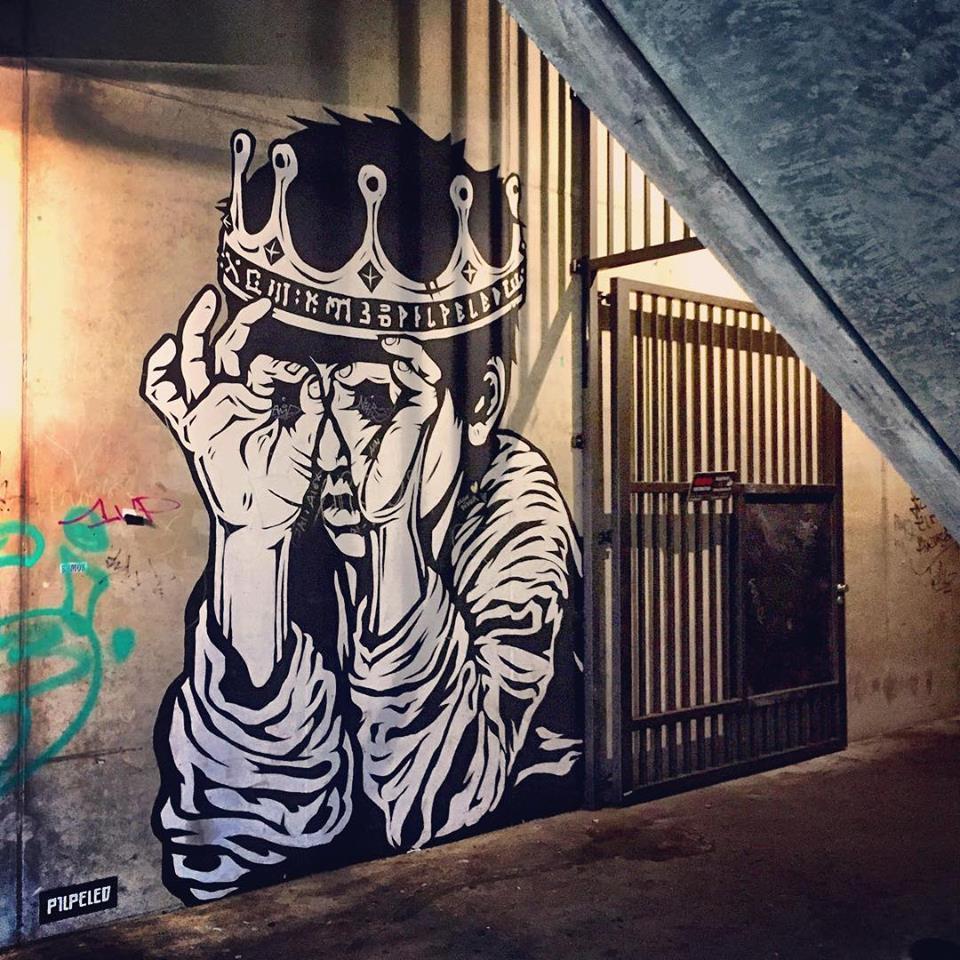 #paracegover Descrição para deficientes visuais: a imagem mostra a entrada em diagonal de um prédio. Na parede lateral, o desenho da parte superior de um menino com uma coroa na cabeça. Ele está brincando de fazer óculos com as mãos. — at Prince Charles.