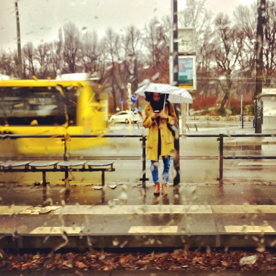 #paracegover Descrição para deficientes visuais: a imagem mostra uma moça de sombrinha branca e capa de chuva amarela esperando o tram e consultando seu smartphone. Acabou de passar um ônibus atrás dela (também amarelo). A cena se passa na frente de um parque em que todas as árvores estão apenas nos galhos. — at Platz der Vereinten Nationen.