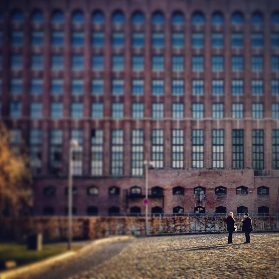 #paracegover Descrição para deficientes visuais: a imagem mostra duas pessoas à distância (em foco) conversando. Atrás delas (desfocado), um maravilhoso prédio industrial cheio de janelas. — at Tempelhofer Hafen.