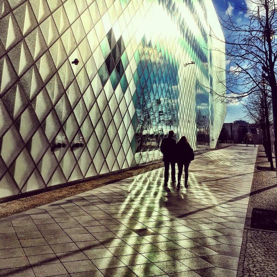 #paracegover Descrição para deficientes visuais: a imagem mostra as silhuetas de um casal caminhando sobre uma calçada. A parede lateral é do centro de exposições Futurium; toda espelhada e com formas geométricas, faz a reflexão do sol parecer uma performance. — at Futurium.