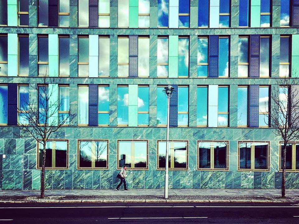 #paracegover Descrição para deficientes visuais: a imagem mostra a fachada de um prédio toda construída em ardósia; as janelas são compridas e refletem o céu. Um homem passa apressado pela calçada. — at Kapelle-Ufer.