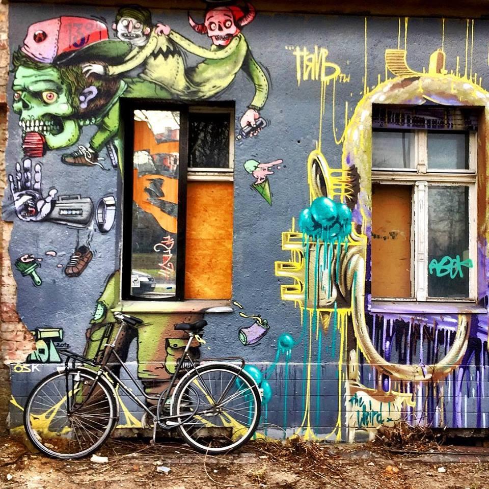 #paracegover Descrição para deficientes visuais: a imagem mostra uma bicicleta estacionada em frente a um prédio cuja fachada está toda grafitada com desenhos de criaturas fantásticas bem coloridas. — at nöldnerstraße.