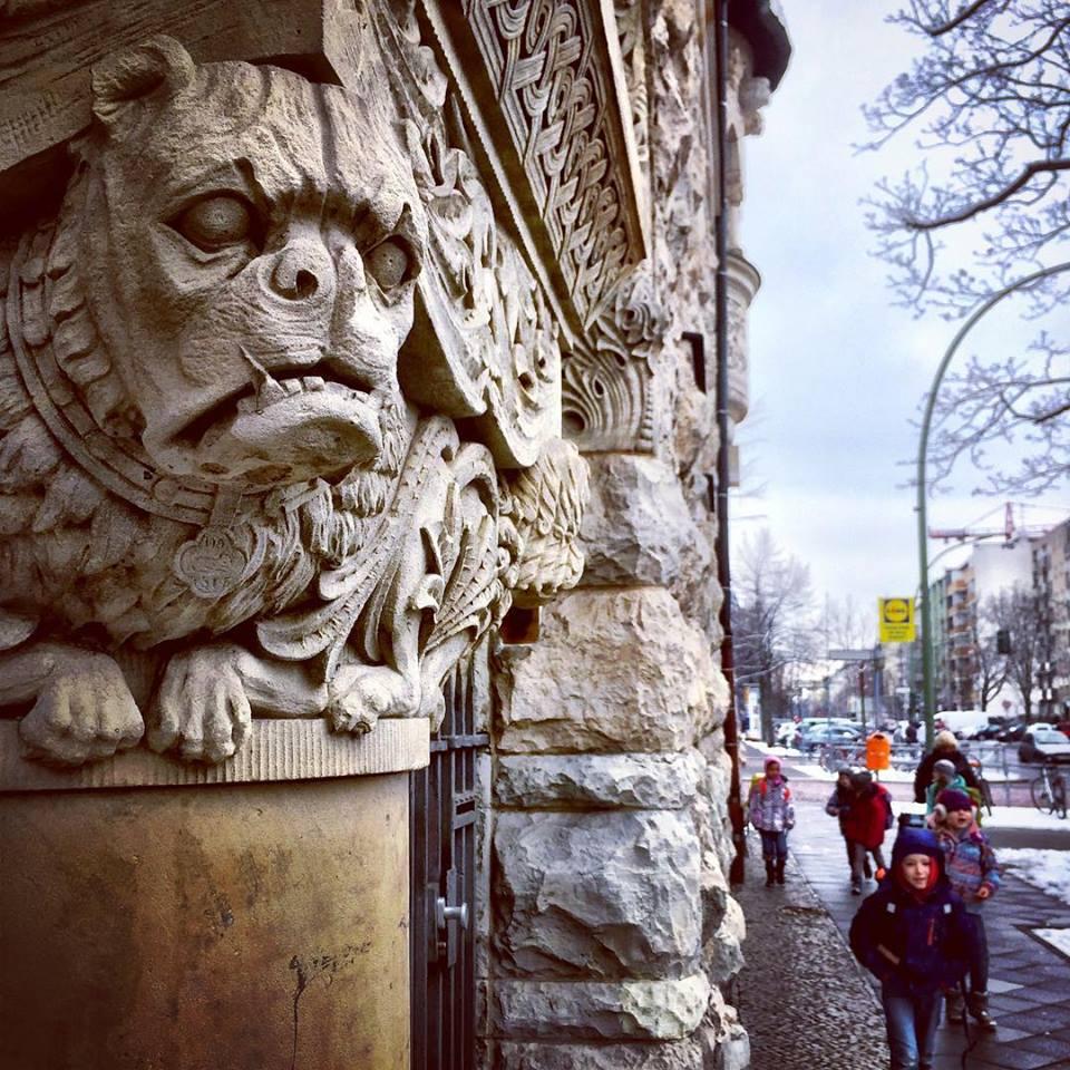 #paracegover Descrição para deficientes visuais: a imagem mostra ima gárgula espreitando as pessoas que passam na calçada. O clima é de suspense... — at Uhlandstraße.