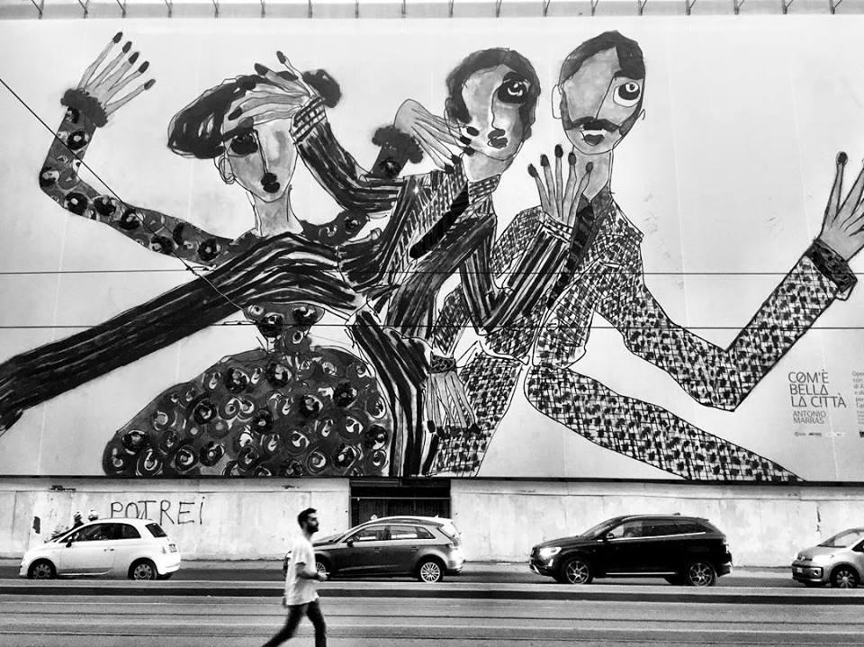 #paracegover Descrição para deficientes visuais: a imagem mostra um mural com três figuras magras e cheais de mãos. Elas parecem assustadas. Há uma pessoa passando pela rua e parece que o trio está surpreso em vê-la. A foto está em preto e branco para destacar as formas.