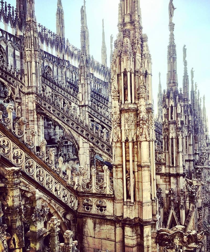 #paracegover Descrição para deficientes visuais: a imagem mostra detalhes arquitetônicos da Duomo de Milão, toda em estilo gótico e cheia de pontas, como se fossem estalagmites. Impressionante.