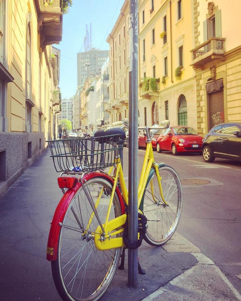 #paracegover Descrição para deficientes visuais: a imagem mostra uma bicicleta com o quadro amarelo e o paralamas traseiro vermelho amarrada a um poste. Há dois carros vermelhos estacionados na rua para combinar. Os prédios são todos amarelos também.