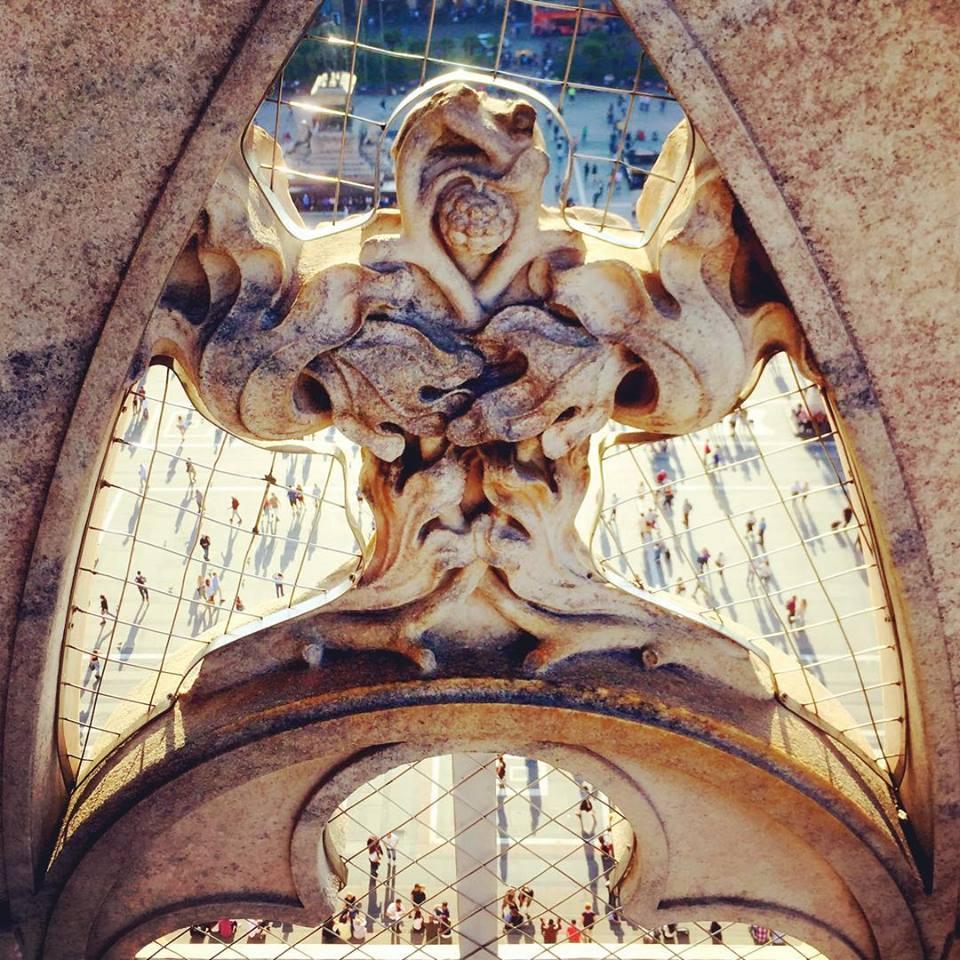 #paracegover Descrição para deficientes visuais: a imagem mostra um arabesco da fachada da igreja que parece um monstro alienígena de pernas abertas. Há uma rede nas partes vazadas, por onde é possível ver as pequenas formiguinhas-pessoas caminhando calmamente.