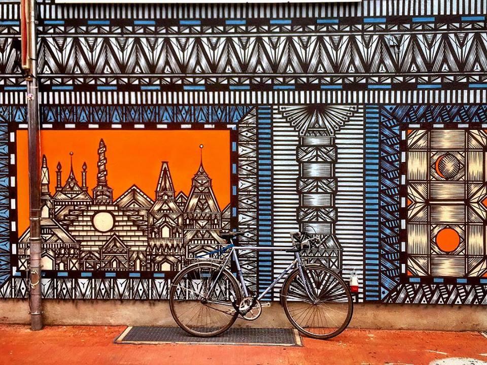 #paracegover Descrição para deficientes visuais: a imagem mostra uma bicicleta estacionada em frente a uma fachada estampada com desenhos incrivelmente detalhados em formas geométricas nas cores azul, laranja e branco. — at Holzmarkt25.
