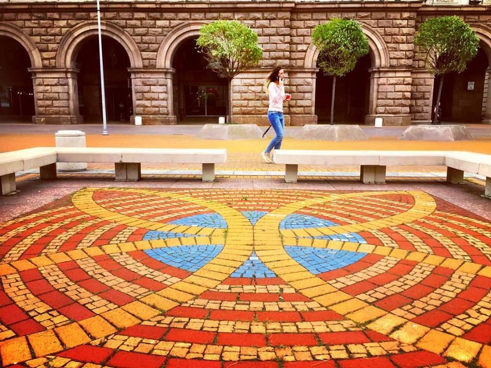 #paracegover Descrição para deficientes visuais: a imagem mostra uma moça caminhando enquanto fala no celular. Em primeiro plano uma calçada com um mosaico nas cores laranja, amarelo e azul. — at Largo di Serdica.