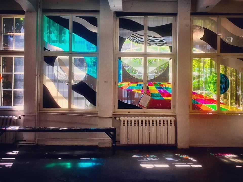 #paracegover Descrição para deficientes visuais: a imagem mostra as janelas ensolaradas de uma exposição de tape art (arte com fitas adesivas). Os vidros estão adesivados com cores diversas. E a exposição fica numa sala atrás de uma livraria especializada em quadrinhos. Delícia!!!! — at Neurotitan.