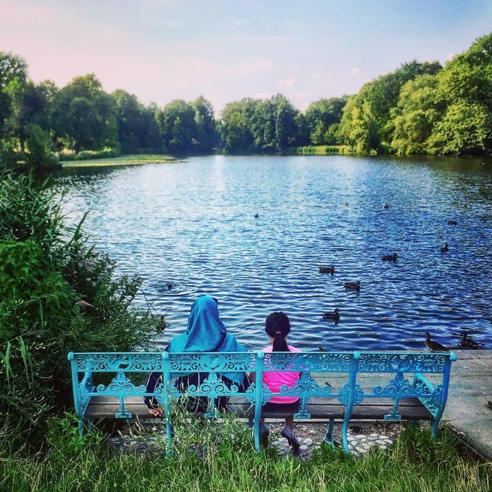 #paracegover Descrição para deficientes visuais: a imagem mostra uma mulher e uma menina de costas, sentadas em um banco de ferro azul. Elas estão contemplando o lago (também azul) dos jardins do Castelo de Charlottenburg. A mulher tem a cabeça coberta com um véu azul. A menina veste uma blusa pink. — at Charlottenburg Palace, Charlottenburg West Berlin.