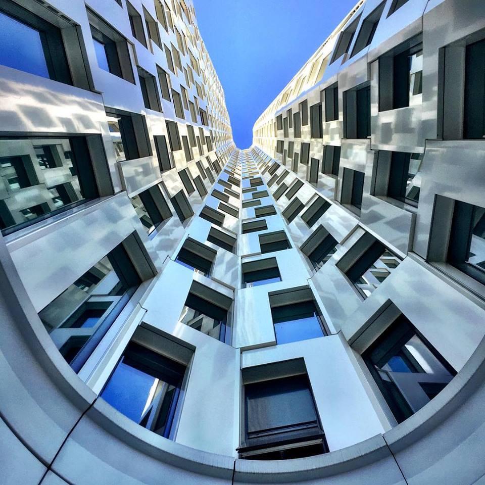 #paracegover Descrição para deficientes visuais: a imagem mostra um prédio curvo visto de baixo para cima. Dessa posição, a fachada parece circular. O céu está profundamente azul. — at Motel One Berlin-Upper West.