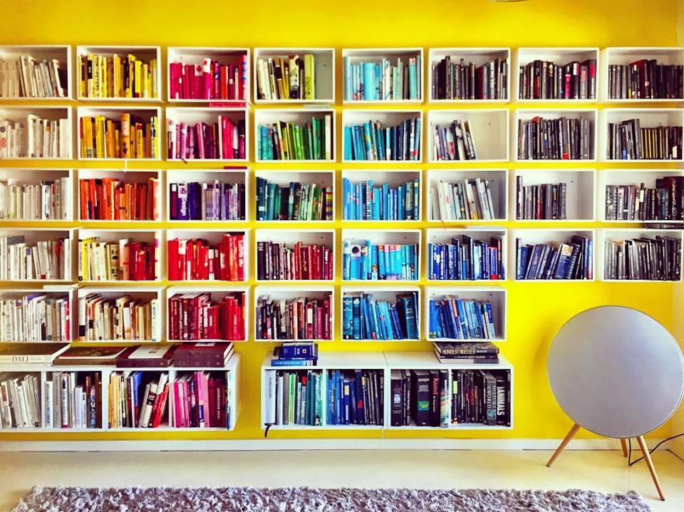 #paracegover Descrição para deficientes visuais: a imagem mostra uma estante de livros formada por 38 caixas de madeira pintadas de branco sobre uma parede amarela (mais 4 caixas para livros maiores da Ikea na parte de baixo). À direita, nicho para a caixa de som em forma de disco com pés de palito. Os livros estão organizados por cores. — in Berlin, Germany.
