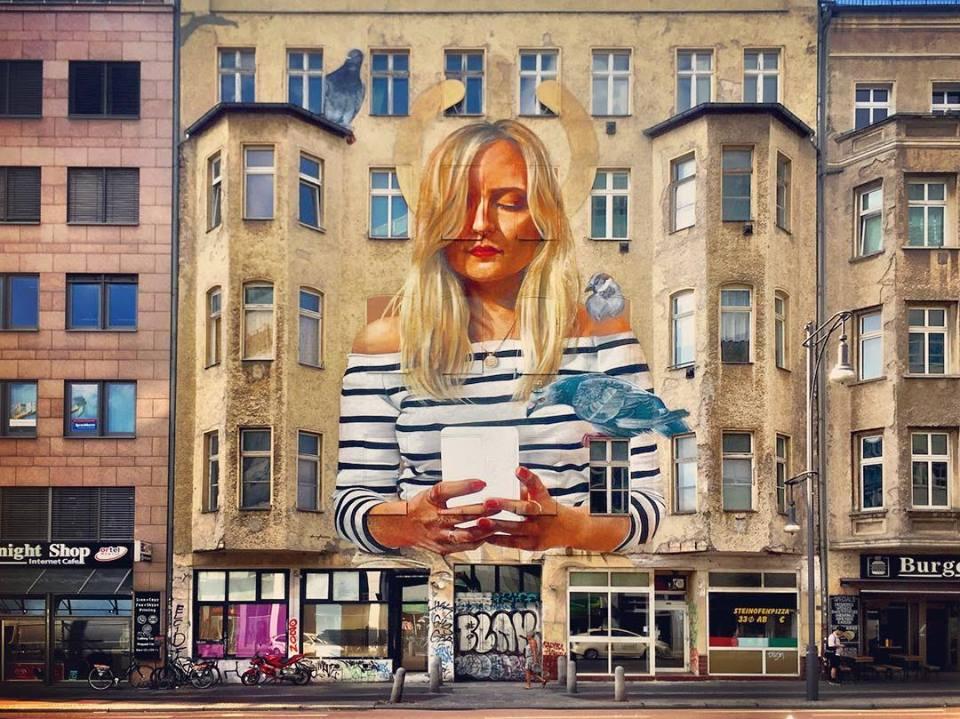 #paracegover Descrição para deficientes visuais: a imagem mostra um prédio antigo com um grafite hiperrealista maravilhoso, em que uma mulher gigante consulta seu smartphone na companhia de pássaros. Ela é loira e usa camiseta listrada. — at PCS PayCard Service GmbH.