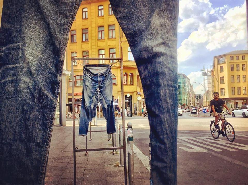 #paracegover Descrição para deficientes visuais: a imagem mostra uma instalação de calças jeans expostas na calçada em frente à loja da Levis. O ponto de vista é por entre as pernas de uma calçada. É possível ver os outros pares de jeans e os prédios amarelos ao fundo. Uma bicicleta passa na rua, do lado direito. — at Buttenheim Levis Icon Store.