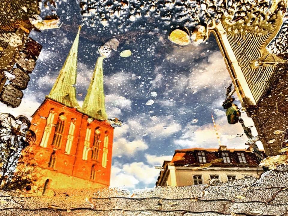 #paracegover Descrição para deficientes visuais: a imagem mostra o reflexo da igreja de São Nicolau, onde começou a cidade de Berlim, refletida numa poça d'água. — at Nikolaiviertel - Heart of Berlin.