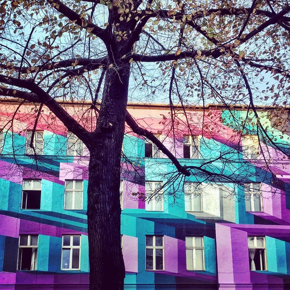 #paracegover Descrição para deficientes visuais: a imagem mostra a fachada de um prédio pintado com formas geométricas que dão um efeito 3D com cores fortes e contrastantes. Em primeiro plano, uma árvore quase sem folhas. — at URBAN NATION.