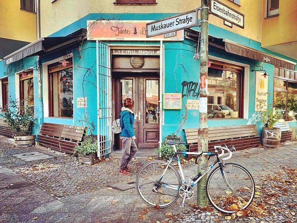 #paracegover Descrição para deficientes visuais: a imagem mostra um café numa esquina da cidade. Há bancos de praça de madeira nas laterais e as paredes são azul turquesa. Em primeiro plano, uma bicicleta estacionada no poste com o nome das ruas. Uma moça está passando pela porta no momento. — at Tante Lisbeth.