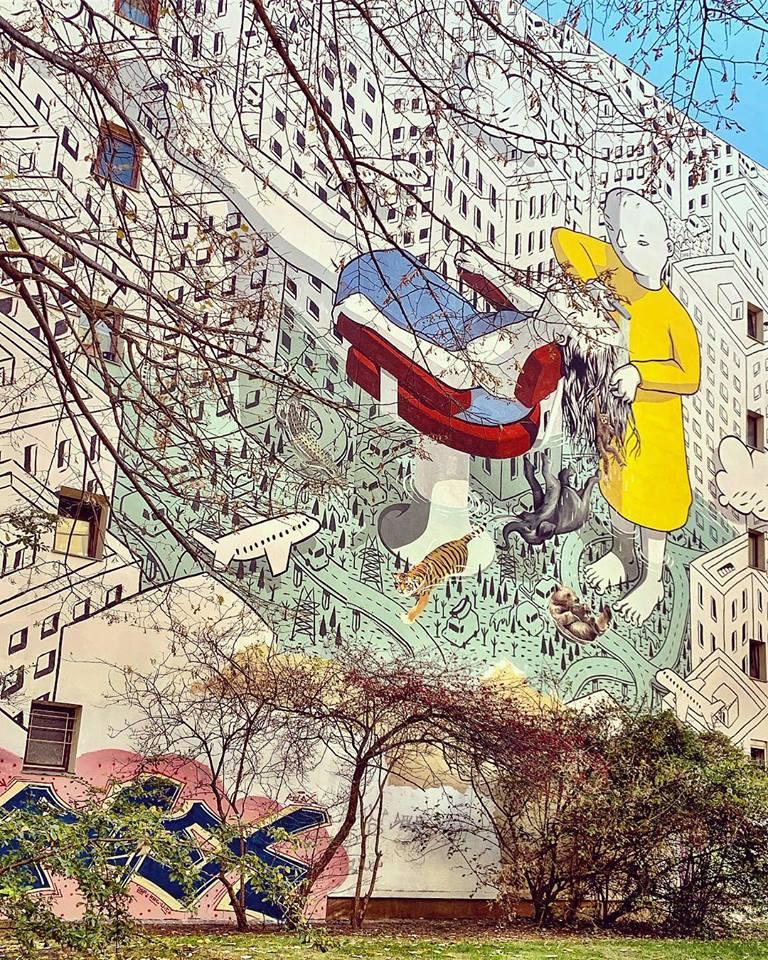#paracegover Descrição para deficientes visuais: a imagem mostra um belíssimo grafite bem detalhado mostrando uma pessoa lavando o cabelo de outra no meio de uma cidade densa de prédios. A água vaza formando um lago colorido e transparente, onde aparecem animais e plantas. Os prédios da cidade são monocromáticos, desenhados apenas em seu contorno. As pessoas, o lago, os animais e as plantas são coloridos. O mural é realmente lindíssimo e está num parque para crianças. — in Kreuzberg, Berlin, Germany.