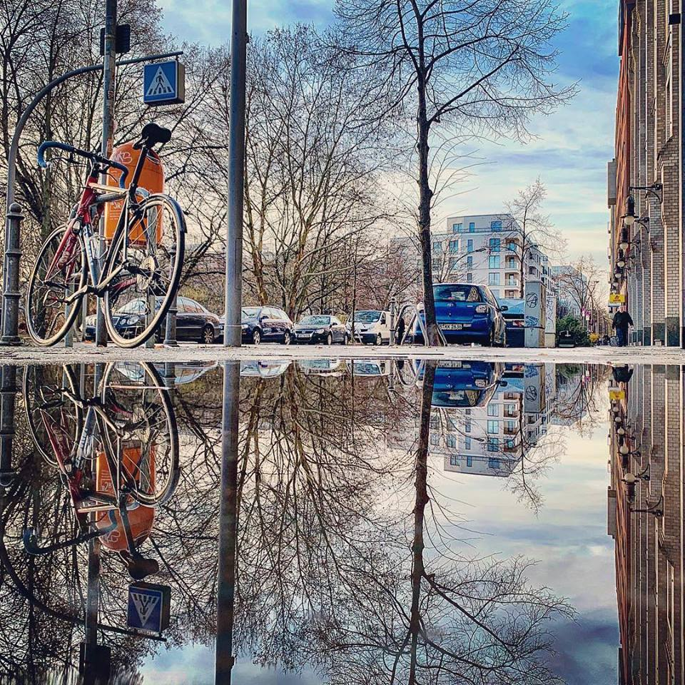 #paracegover Descrição para deficientes visuais: a imagem mostra o reflexo da calçada numa poça d'água: uma bicicleta parada ao lado de uma lixeira laranja; um carro azul, parte da fachada de um prédio e uma floresta de galhos secos. Depois de dias cinzentos, o céu acordou azul... — at Alnatura.