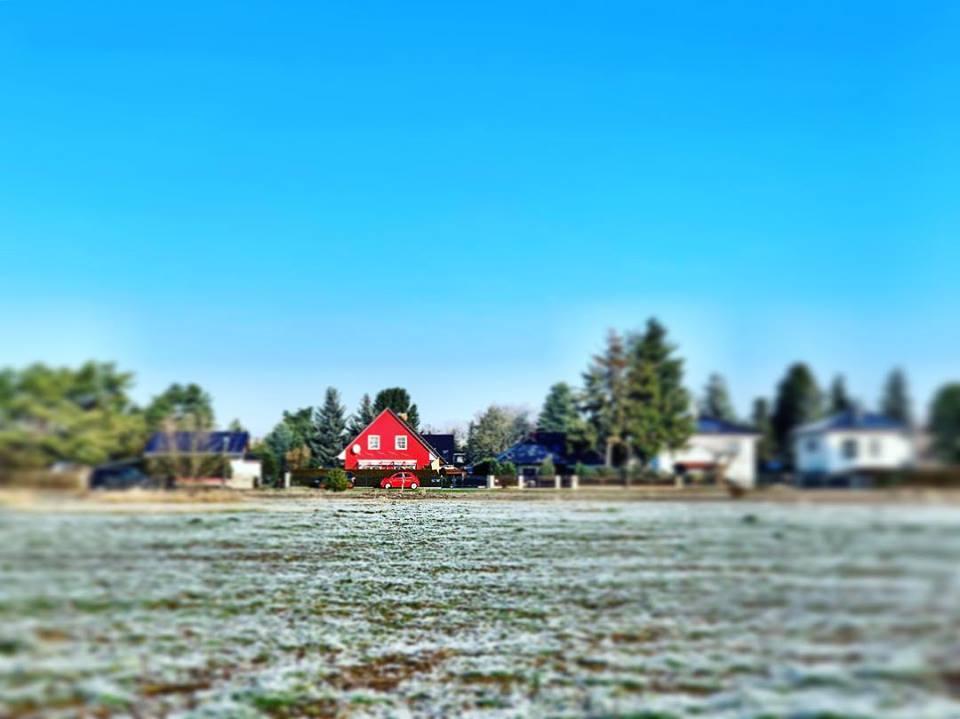 #paracegover Descrição para deficientes visuais: a imagem mostra um campo gramado coberto de gelo. Ao fundo, casas diversas; a que está em foco é um chalé vermelho com um carro da mesma cor estacionado em frente. Nem sempre odeio carros...rsrs — in Mahlsdorf, Berlin, Germany.
