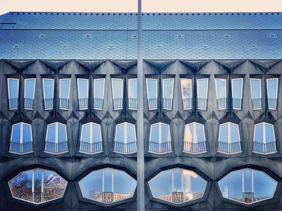 #paracegover Descrição para deficientes visuais: a imagem mostra a fachada de um prédio com os vidros espelhados e janelas com formas geométricas não usuais. — at Alte Münze Berlin.