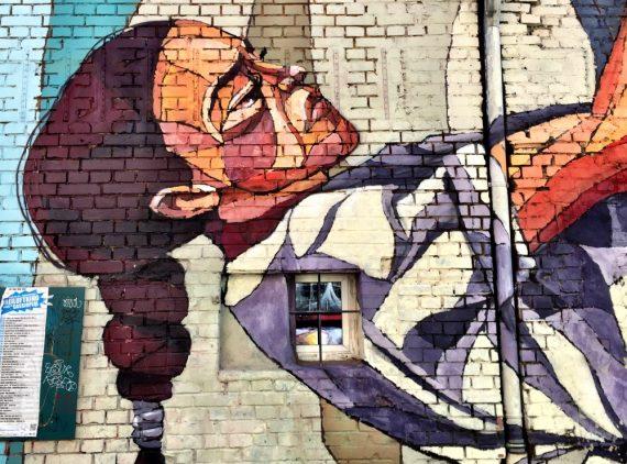 A imagem mostra um grafite que representa o tronco de uma mulher escalando uma parede. Ela está de lado.