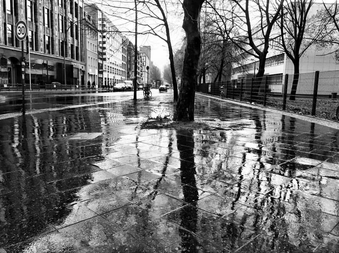 #paracegover A imagem mostra uma foto em preto e branco de uma rua totalmente molhada pela chuva. A calçada reflete os prédios e as árvores sem folhas. — at Märkisches Museum (Berlin U-Bahn).