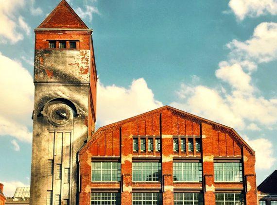 A imagem mostra uma fábric cuja torre onde está instalado o relógio apresenta uma instalação de um olho humano bem assustador.