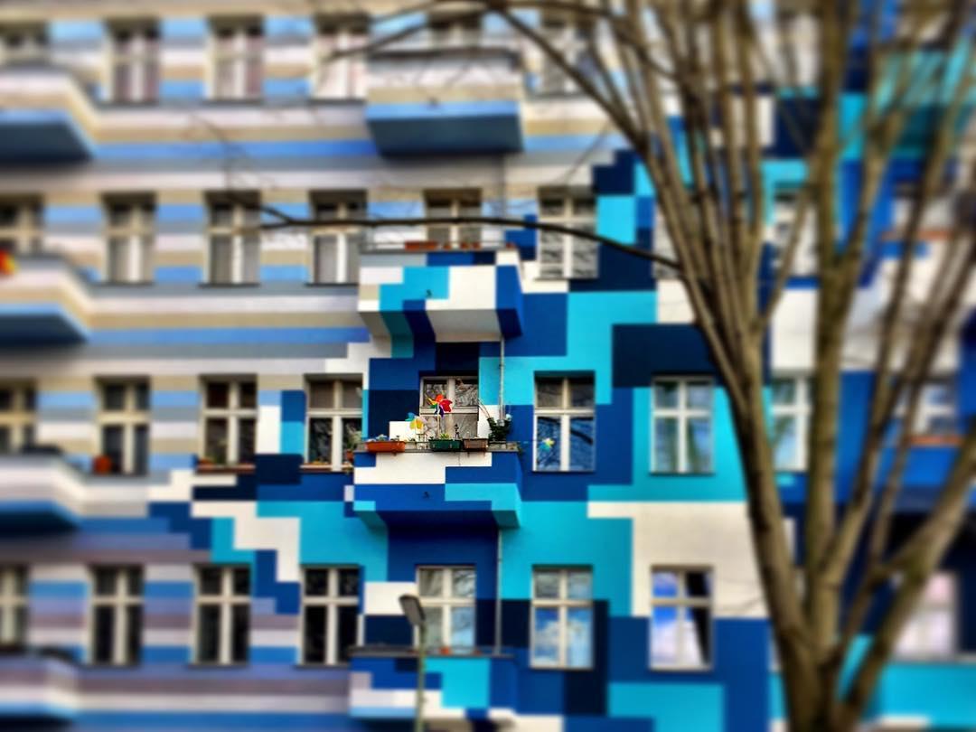#paracegover Descrição para deficientes visuais: a imagem mostra a fachada de um prédio que seria comum não fosse a ousadia e criatividade de pintar os element de volume em tons diferentes de azul, indo do lilás ao turquesa. Do lado direito à ênfase está nos quadrados e retângulos sobrepostos. Do lado esquerdo, listras. Em destaque, uma sacada típica alemã, com decoração eclética e bem colorida. — at Innstraße berlin.
